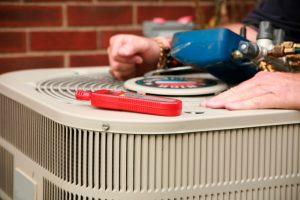 HVAC technician doing repairs on the outdoor unit of an air conditioner