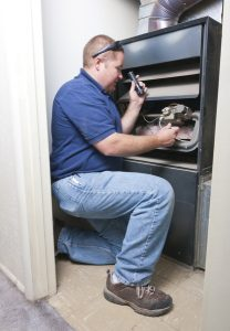 technician inspecting the inside of a heating system