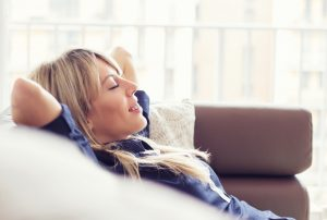 relaxed young woman laying back on couch in comfortable home