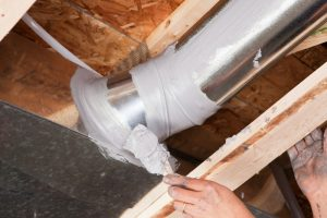a hand professionally sealing off heater ductwork