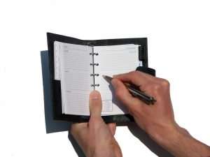 person's hands writing in daily planner