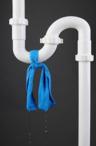white pipe with blue cloth tied around leak