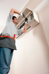 technician-making-repairs-to-ductless-air-handler