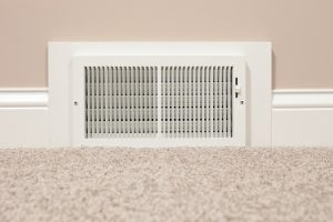 vent-on-wall-near-baseboard-with-carpeted-floor-in-forefront