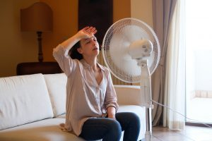 woman-looking-hot-sitting-in-front-of-fan