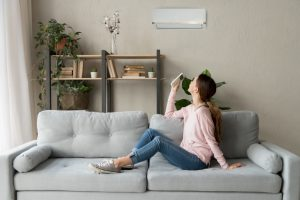 woman-witting-on-couch-turning-ductless-air-handler-on