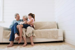 family-sitting-on-beige-couch-in-home-smiling
