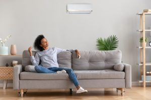 woman-sitting-in-modern-living-room-enjoying-breeze-from-ductless-air-handler