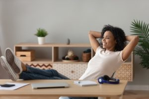 woman-with-feet-on-desk-looking-comfortable-and-happy-indoors