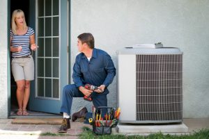 technician-installing-air-conditioner-and-homeowner-standing-nearby