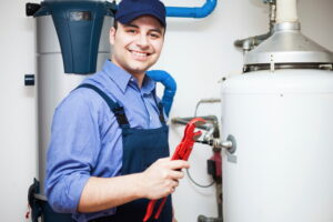 technician-smiling-and-standing-by-water-heater-tank-with-wrench-in-hand